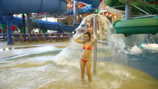 Woman stands under a fountain in a pool in indoor water park