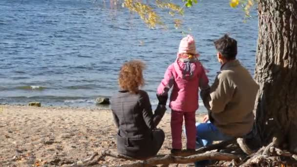 Family sits under tree on bank