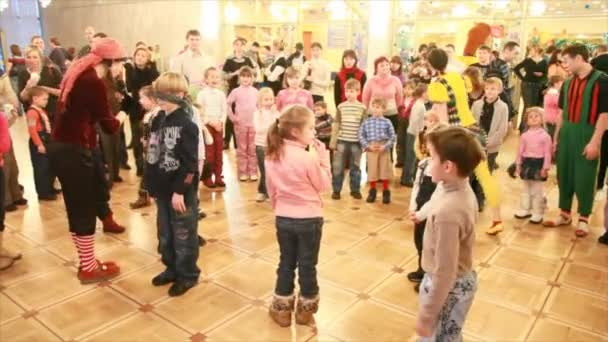 Adults hold competitions with participation of children in hallway of circus.