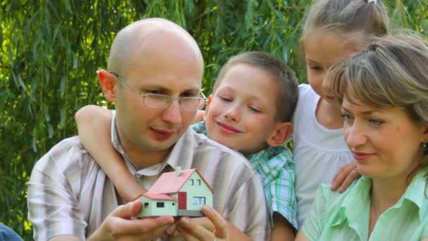 rodiny čtyř sedí v parku a dobře podívat na dům hraček