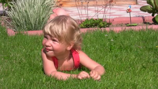 portrét roztomilá holčička leží na zelené trávě v zásuvce a visí nohy