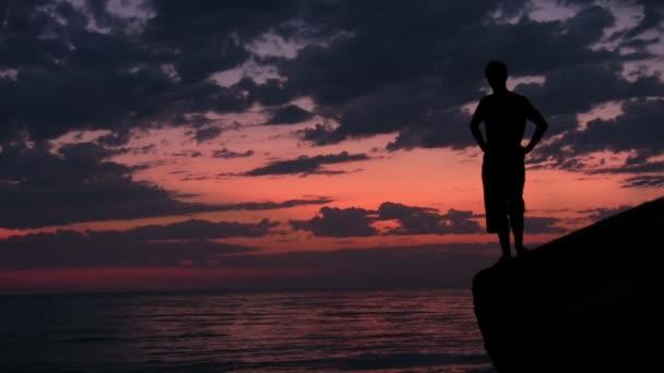 silhouette del giovane uomo si leva in piedi sulla roccia contro il tramonto