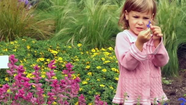 Malá holčička drží v ruce fialový lístek a zkoumá, stojící v parku