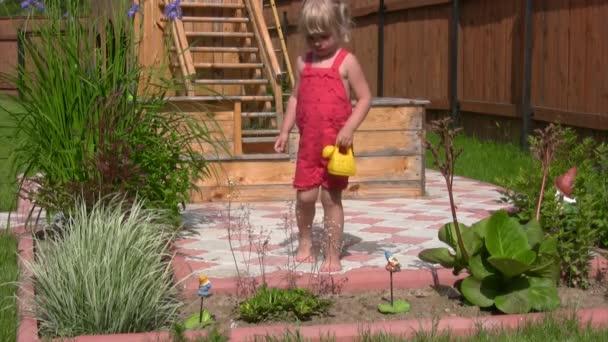 holčička s konev odlévání na květiny v zahradě