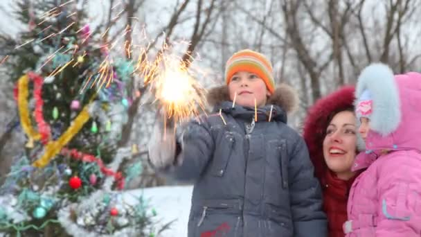 Happy family of three with sparkler against decorated Christmas tree outdoor
