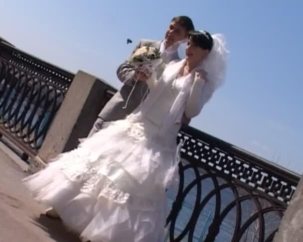 nevěsta a ženich drží kytici a představuje proti řeka