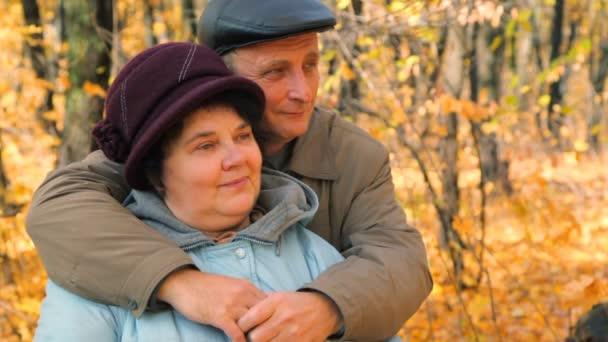 starší pár objímání proti stromy v parku