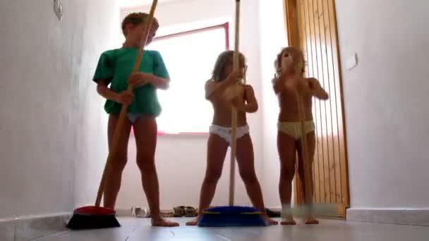 Three children dance with mops, indoor.