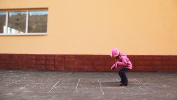 Boy and girl playing hopscotch jumping