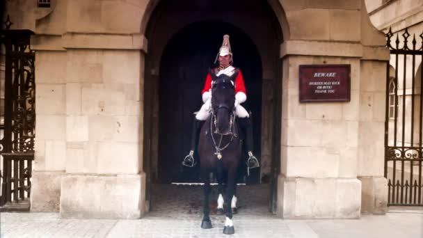 Guard in uniform sits on horseback near Horse Guards building in London, UK.