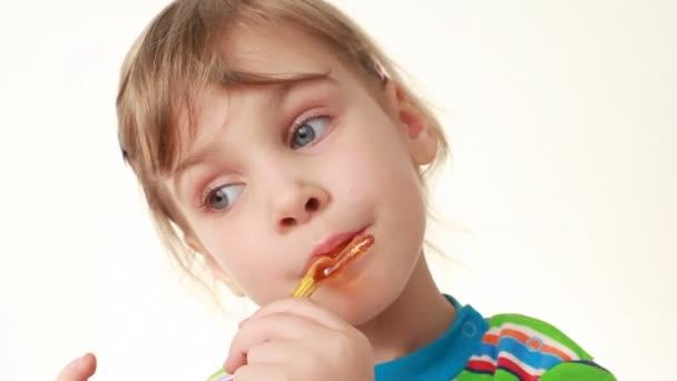 malá holčička olizování lízátka v podobě kuřete