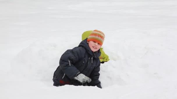 malá dívka a chlapec sedí mezi sněhem, hází, komorní v zimě ráno