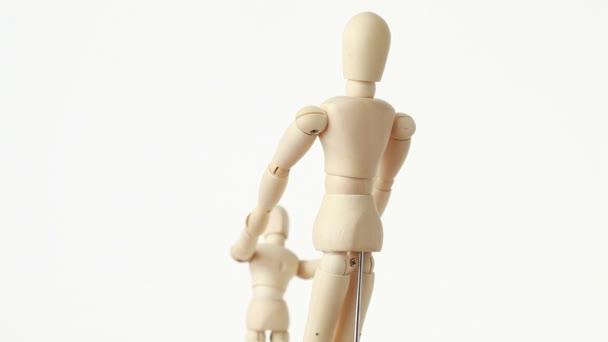 親と彼の子供の木像が手をつないでいます。
