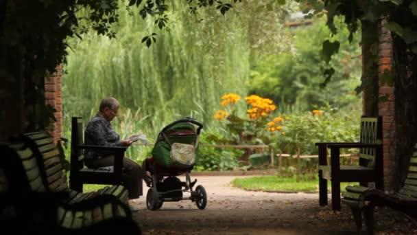 Gelassener alter Mann liest Zeitung auf Bank neben Kinderwagen