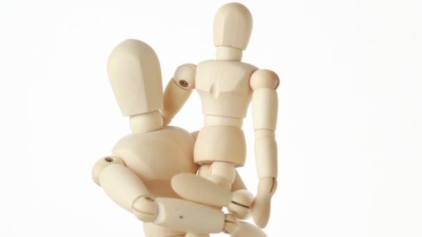 dřevěné postavy dítěte na rukou jeho rodiče