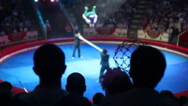 Silhoettes Publikum schaut Leistung mit Turner im Zirkus