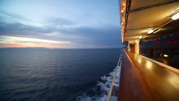 žena chodí na osvětlené palubě výletní lodi