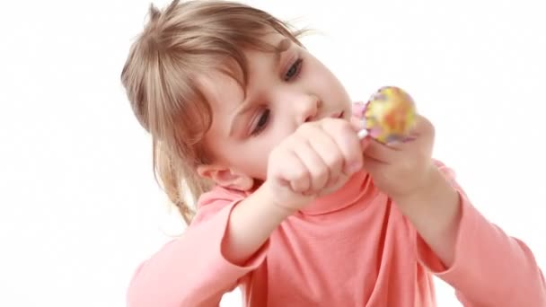 Little girl trying to remove cover of lollipop