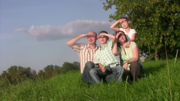 Family sits in a grass and looks afar.