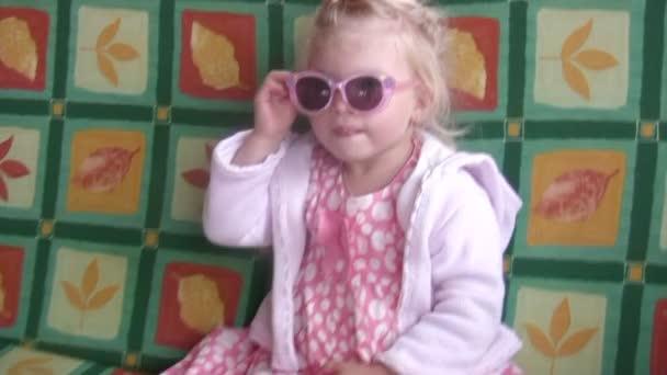 malé holčičky v brýle a růžových šatech se třese na houpačce