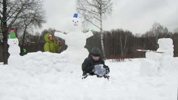 dvě malé děti hrají ve sněhu sochařské sněhulák, časová prodleva