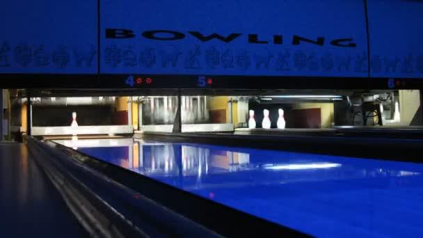 stroj se kuželek, bowlingu svítí v tmavém klubu