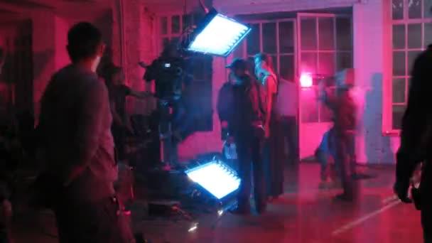 Lighting technicians adjust light equipment while filming video