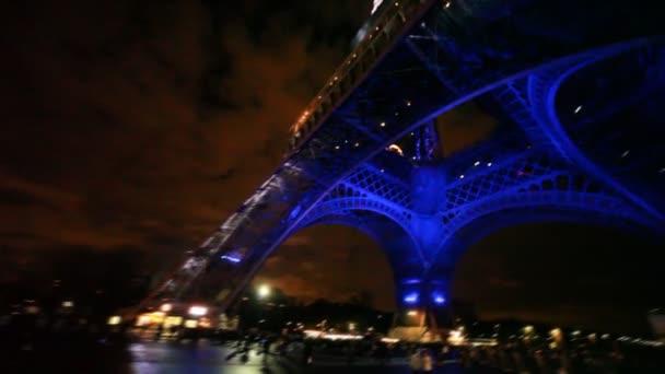Eiffelova věž svítí v noci na pozadí oblohy