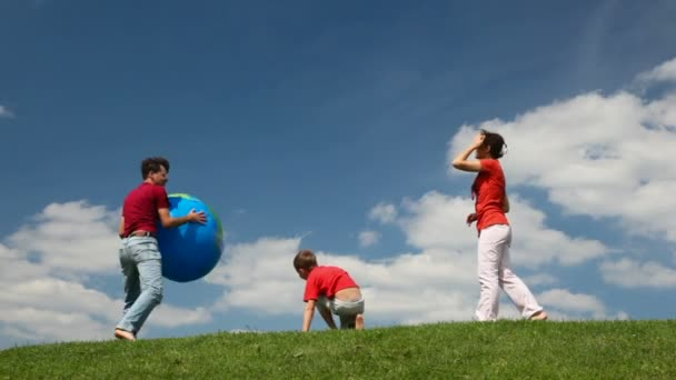 Parents and son playing big inflatable ball on meadow
