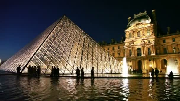 Tourists walk near piramid in front of Louvre