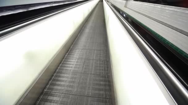 eskalátor a nohy lidí, kteří jdou na ní v Paříži letiště
