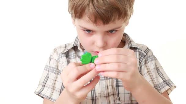 chlapec se snaží přidat poslední část hraček a to vypadá, jako to udělal