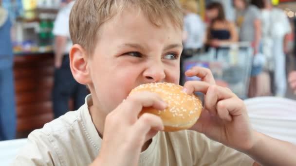 Kavkazská chlapec jíst hamburger v kavárně