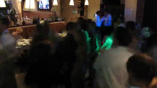 Some people sit at table while other dance at wedding party