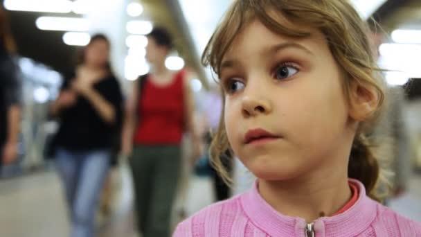 roztomilá holčička stojí uvnitř metra