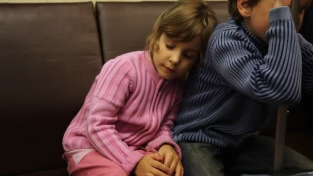 Nice little girl sits and sleeps leaning to back of his brother in riding subway train, then wakes up