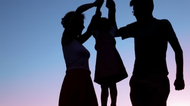 Silhouettes of parents holds and raises little daughter