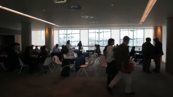 People sit at the discussion tables in the meeting hall