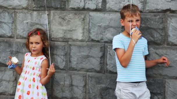 chlapec a dívka stojící, jíst zmrzlinu