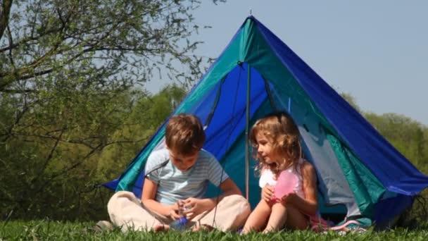Fiú és lány üveg sit sátorban, kinyitja a palackozott víz