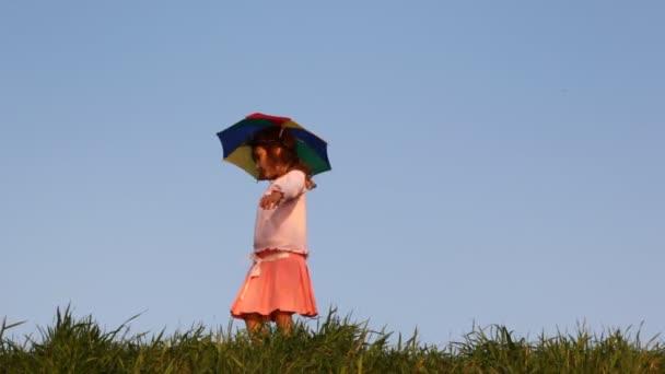 Kleines Mädchen mit Hut als Regenschirm dreht sich auf Gras