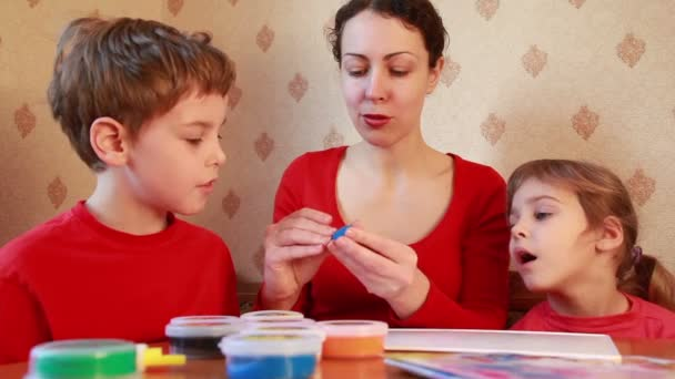 Woman works with children on table, boy sculpts figure plasticine