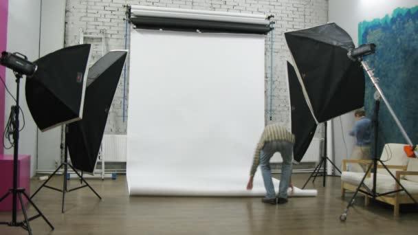 Photographer and his kid adjust lightening at photo studio