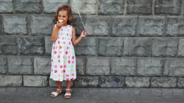 holčička stojí, jí zmrzlinu