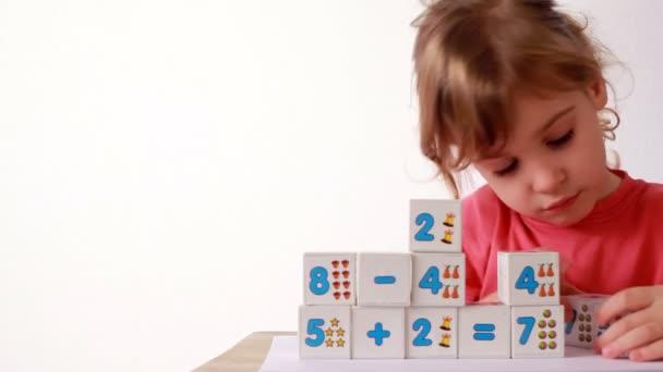 dívka staví dřevěné bloks s čísly, přidává kostičky