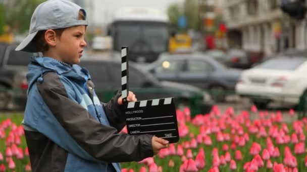 Boy with cinema clapper board hands stands on streets