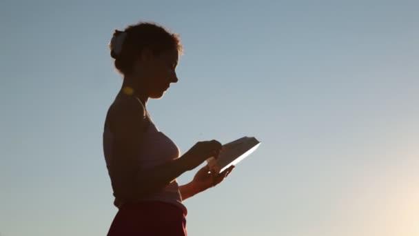 silhouette di donna con libro