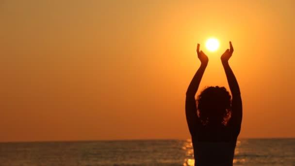 Žena stojící na pláži, v ruce držel slunce