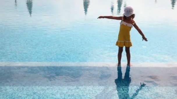 dívka stojí ve vodě v bazénu a zdvižené ruce ohyby doprava a doleva