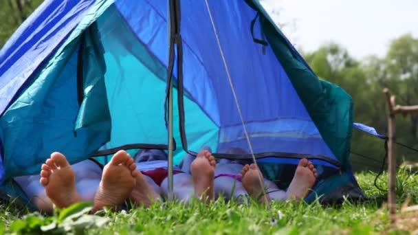 rodina s bosýma nohama leží ve stanu v lese na den, a pak chlapec sedí